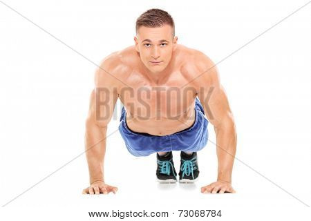 Athletic man doing pushups and looking at camera isolated on white background
