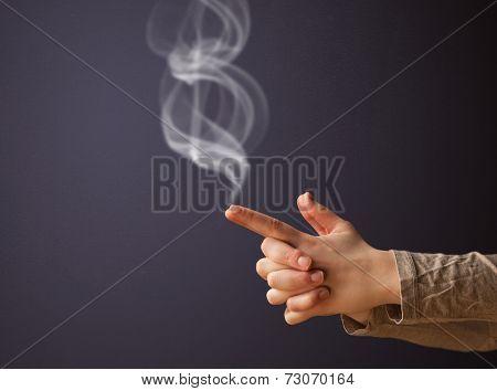 Gun shaped woman hand with smoke