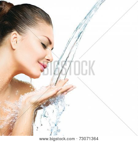 Beautiful Model Girl with splashes of water in her hands. Beautiful Smiling Woman under splash of water with fresh skin over blue background. Skin care Cleansing and moisturizing concept. Beauty face