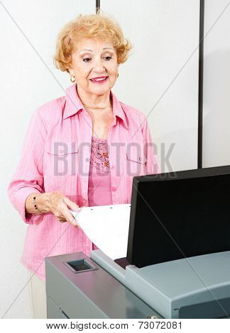 Senior woman using a new optical scanner voting machine to cast her ballot.