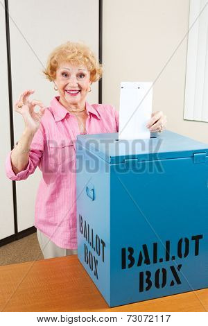 Senior woman drops her ballot in the box and gives A Okay sign.