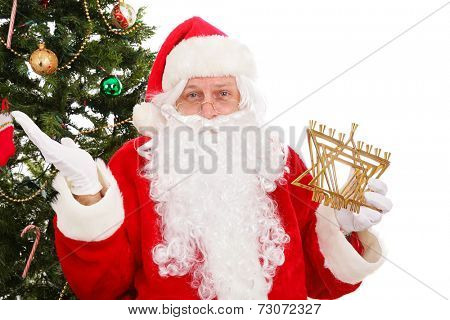 Santa standing in front of a Christmas tree holding a menorah.