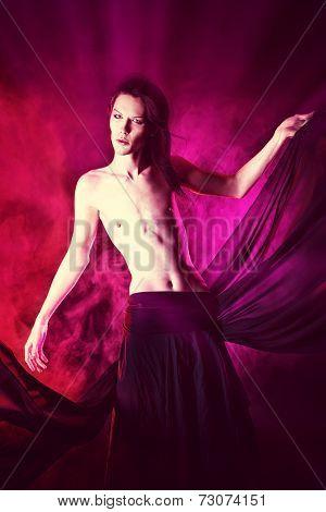 Art photo of a beautiful graceful brunet man dancing with airy black chiffon. Fashion.