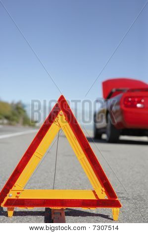 Warning triangle in front of broken down red sports car at side of road