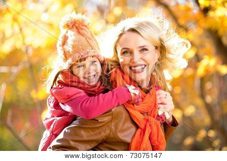 Smiling parent and kid family walking together outdoor in yellow fall or autumn park. Happy child sitting on mother's back.