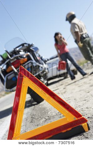 Warning triangle behind police motorcycle and stopped car