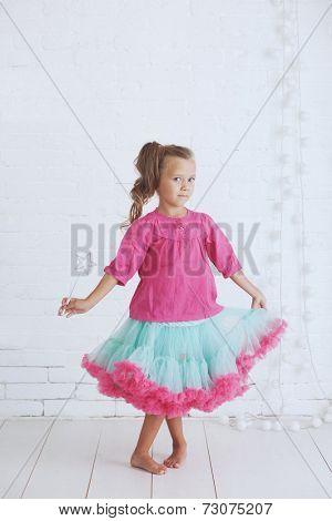 Studio portrait of cute little princess girl wearing holdiday candy tutu skirt holding magic wand
