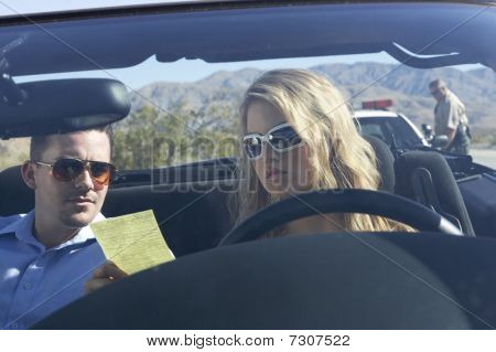 Couple sitting in car looking at traffic ticket