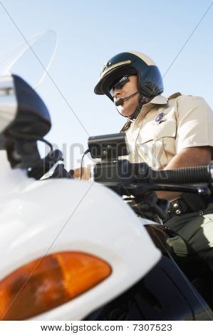 Police officer sitting on motorcycle low angle view (low angle view)