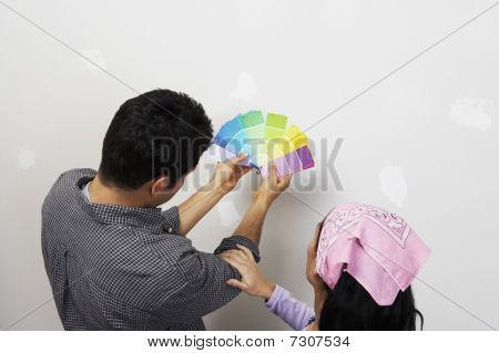 Couple looking at paint samples near interior wall back view elevated view