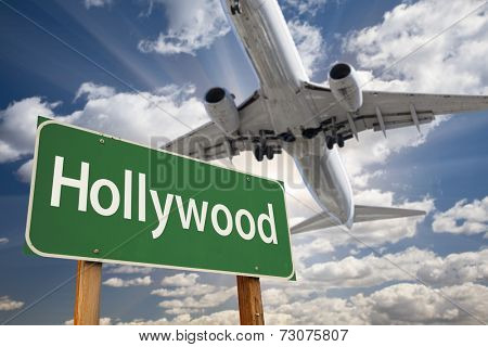 Hollywood Green Road Sign and Airplane Above with Dramatic Blue Sky and Clouds.