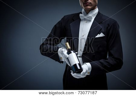 Man in a tuxedo with a bottle wine