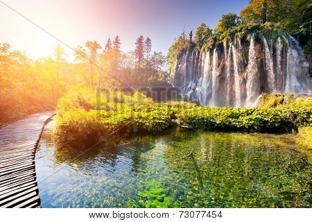 Majestic view on waterfall with turquoise water and sunny beams in Plitvice Lakes National Park. Forest glowing by sunlight. Croatia. Europe. Dramatic morning scene. Beauty world. Instagram effect.