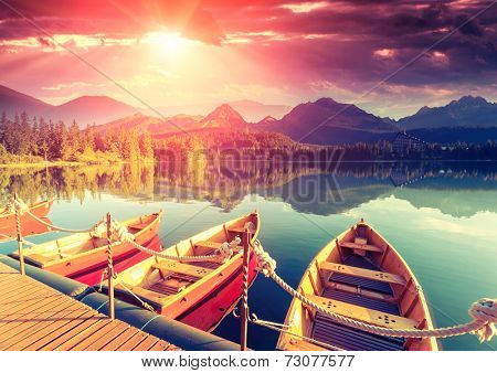 Majestic mountain lake in National Park High Tatra. Dramatic unusual scene. Sky glowing by sunlight. Strbske pleso, Slovakia, Europe. Beauty world. Retro style filter. Instagram toning effect.