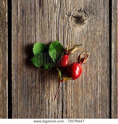 Rose hip over old wooden background with copy space