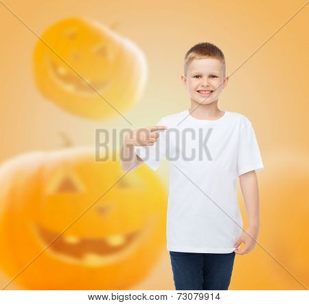 holidays, childhood, happiness, gesture and people concept - smiling little boy in white blank shirt pointing finger at himself over halloween pumpkins background
