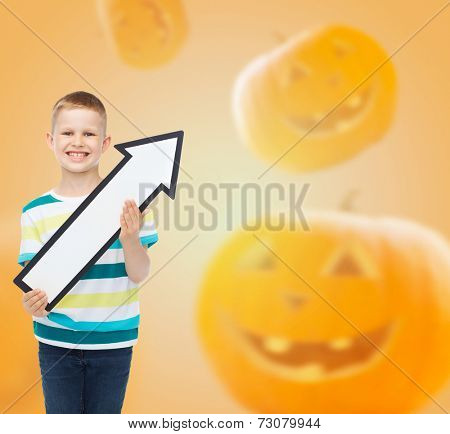 advertising, direction, holidays and people - smiling little boy holding big white arrow over halloween pumpkins background