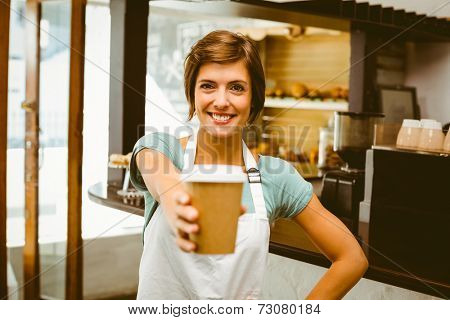 Pretty barista smiling at camera holding disposable cup at the coffee shop
