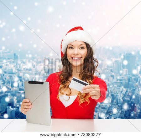 christmas, technology, shopping and people concept - smiling woman in santa helper hat with tablet pc computer and credit card over snowy city background