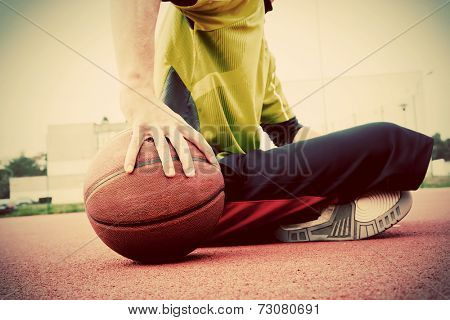 Young man on basketball court. Sitting and dribbling with ball. Streetball, training, activity. Real and authentic, vintage mood.