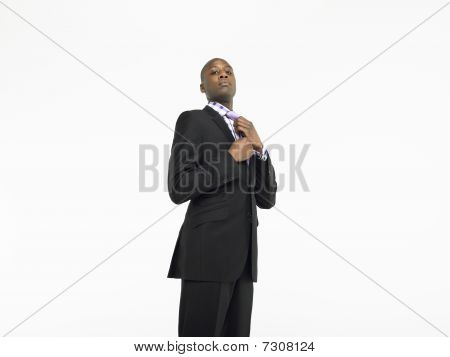 Businessman adjusting tie in studio