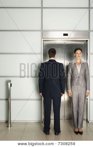 Businesspeople standing In and Out of Office Elevator