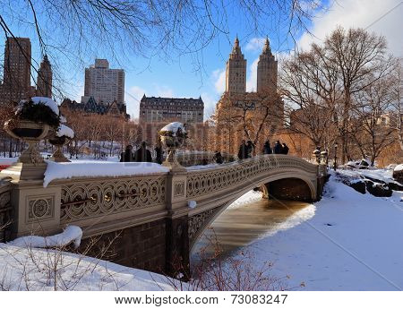 New York City Manhattan Central Park panorama in winter with ice and snow over lake with bridge,  skyscrapers and blue cloudy sky at dusk.
