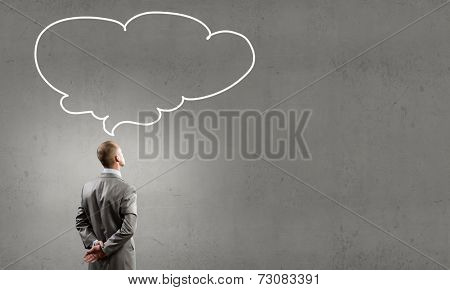 Rear view of businessman looking up thoughtfully