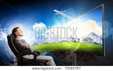 Young businessman sitting in chair behind tv