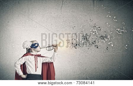 Cute girl of school age in superhero costume playing trumpet