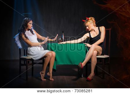 Angel and devil with brandy glass in dark room