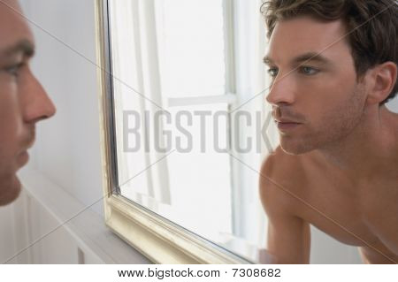 Man examining reflection in mirror