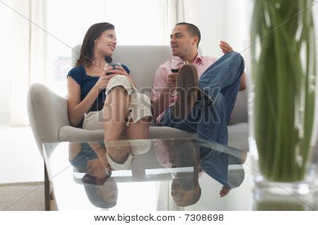 Couple drinking wine talking on sofa