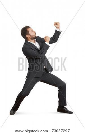 young businessman in formal wear beating his fist. isolated on white background