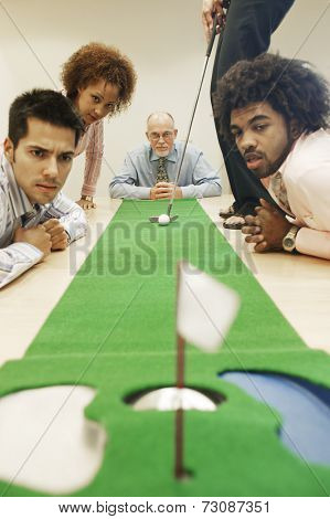 Group of businesspeople watching businesswoman aim golf ball