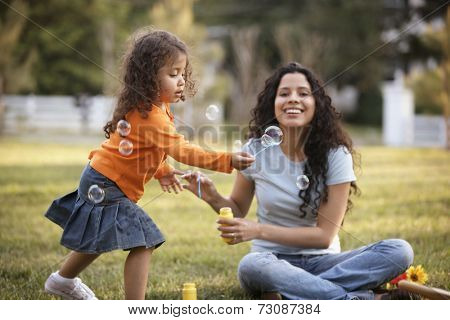 Mother and daughter blowing bubbles outdoors