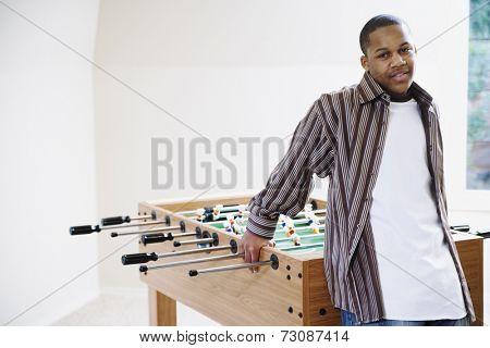 Boy standing beside foosball table