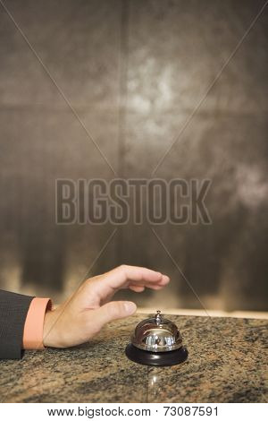 Hand reaching for service bell on counter