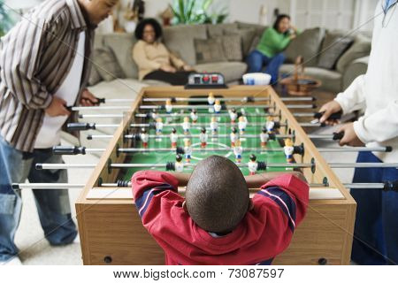 Family watching foosball game