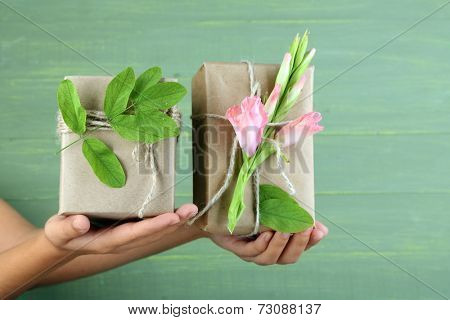 Female hand holding natural style handcrafted gift boxes with fresh flowers and rustic twine, on wooden background