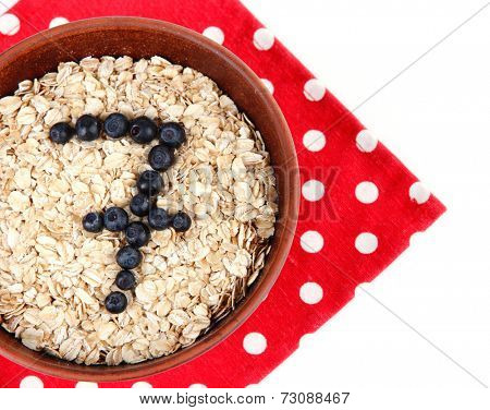 Brown wooden bowl with oatmeal and bilberries on a square polka dot napkin isolated on white