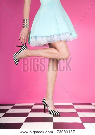 Young woman standing on one leg wearing high heels