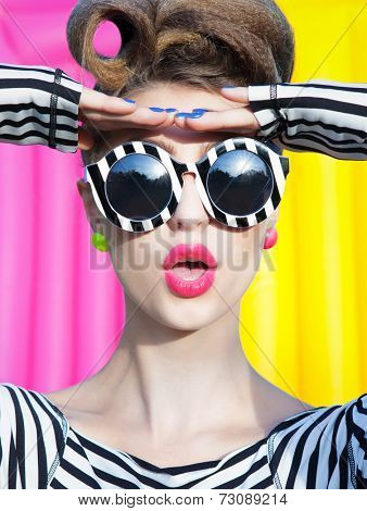 Colorful portrait of young attractive surprised woman wearing stripy sunglasses