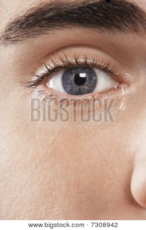 Man's blue eye crying