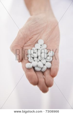 Senior woman holding out hand full of pills close-up on hand