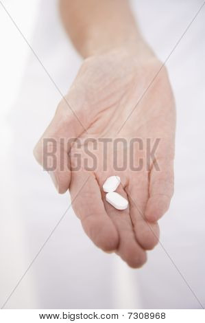 Senior woman holding pills in hand close-up on hand