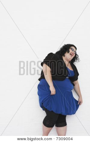 Mulher com sobrepeso, rindo enquanto curtseying