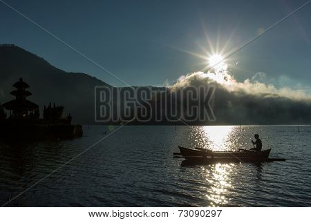 silhouette of a fisherman in a traditional out-rigger paddle boat across Lake Bratan, Bali Island
