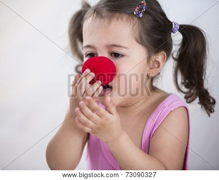 Cute girl wearing clown nose at home
