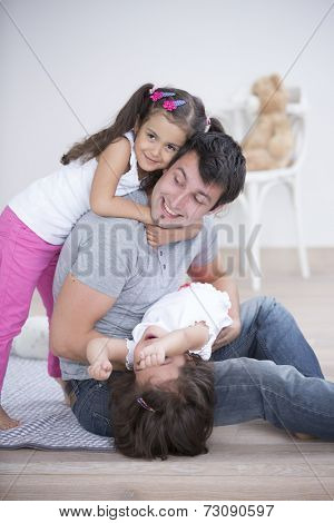 Father with playful daughters at home